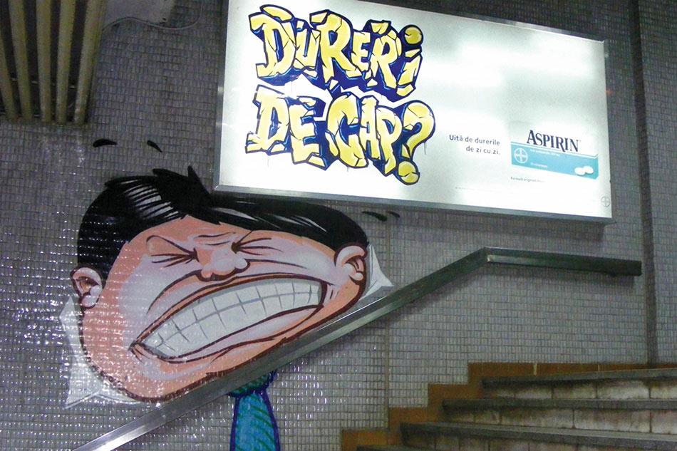 Bilbord ćoškom pritiska glavu muškarca na drzač rukohvata - reklamiranje firme Bayer