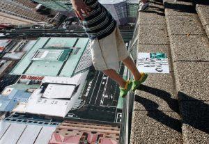 Dete poleće sa stepenika na poster sa oblakoderima reklamiranje maksimalne vožnje