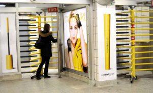 Devojka gura obrtna vrata maskaru i gleda u reklamiranje firme CoverGirl