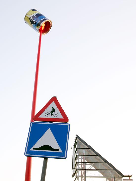 Levis limenka boje na vrhu stuba iza saobraćajnih znakova - reklamiranje firme
