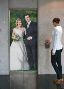Mlada i mladoženja na vratima lifta u prirodnoj veličini