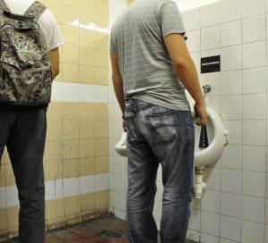 Levi muškarac urinira u pisoar a desni čita reklamamiranje Romanian Police