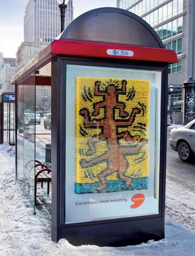 Olovkasto trostruko narandžasto biće na billboard-u buske stanice - reklamiranje firme Deserres