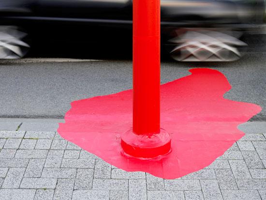 Podnožje bandere na trotoaru crveno izlivanje