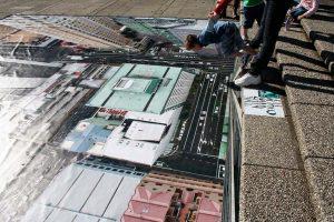 Roditelj drži dete koje je spremno za skok na poster visokih zgrada reklamiranje maksimalne vožnje