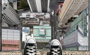 Starke patike na ivici stepenika i poster sa pogledom na nebodere reklamiranje maksimalne vožnje