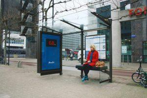 Žena sedi na klupi na buskoj stanici i gleda reklamiranje Fitness First