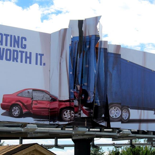 Zgužvani bilbord između auta i kamiona reklamiranje Colorado State Patrol-a